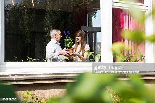 Young woman handing grandfather a plant in house