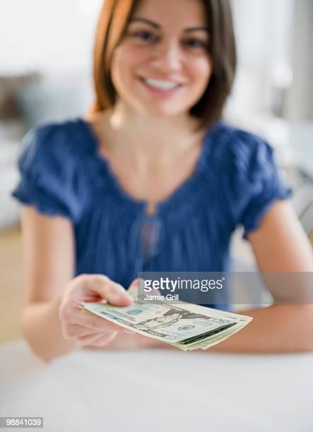 Young woman handing money towards camera