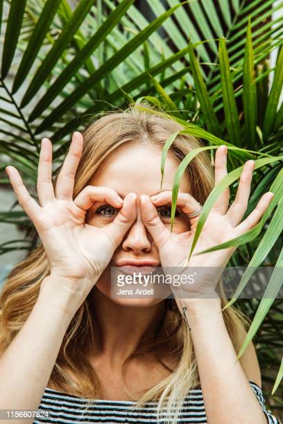 young woman hands around eyes, woman fingers around eyes, woman making silly face, snooping, nosy neighbor, spying on someone - チラッと覗く ストックフォトと画像