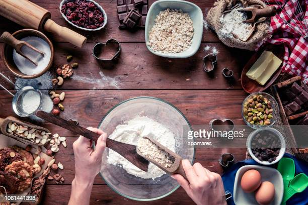 Young woman hands mixing ingredients for chocolate and nuts cookie making