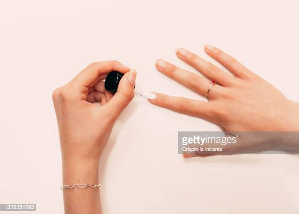 young woman hands painting nails with white polish, on white background, close-up - white nail polish stock pictures, royalty-free photos & images