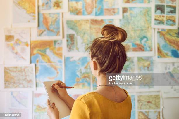 young woman handwriting at notebook while looking at map - europa geografische locatie stockfoto's en -beelden