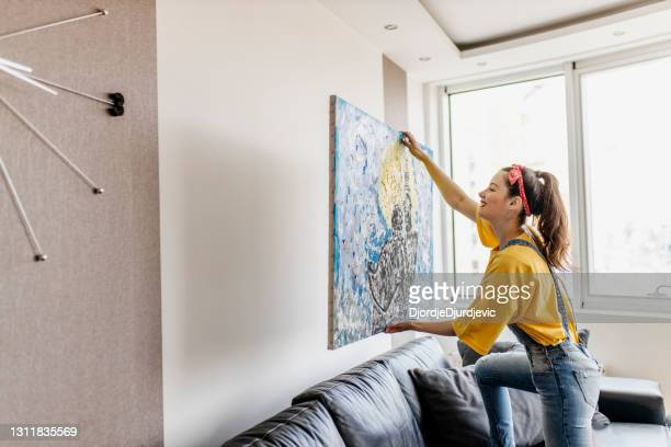 young woman hanging art picture on wall and decorating living room - hanging stock pictures, royalty-free photos & images