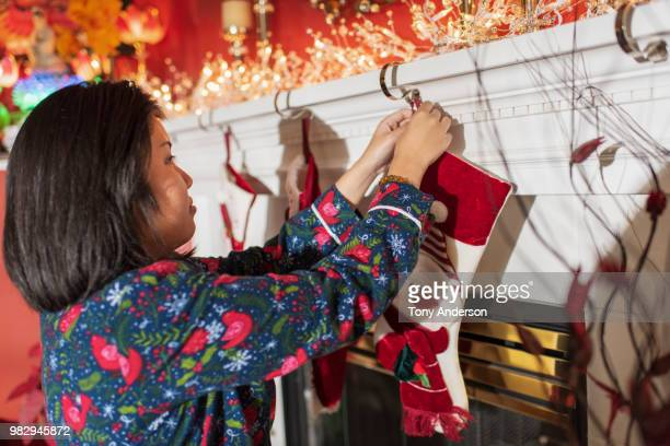 young woman hanging christmas stocking on hearth - femme bas photos et images de collection
