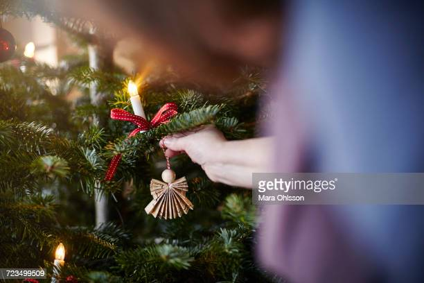 Young woman hanging decoration on Christmas tree, close-up