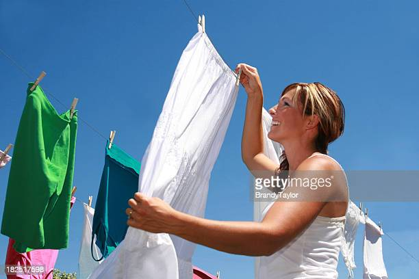 A young woman hanging her laundry to dry outside