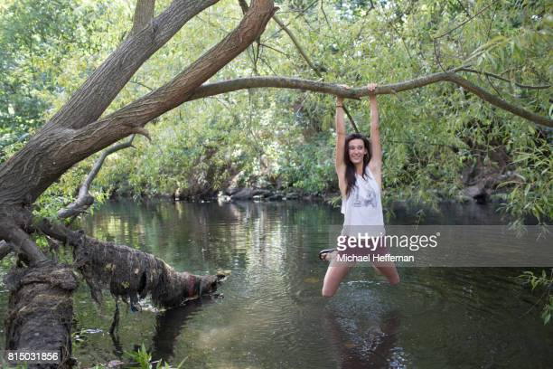 Young woman hanging off tree over river