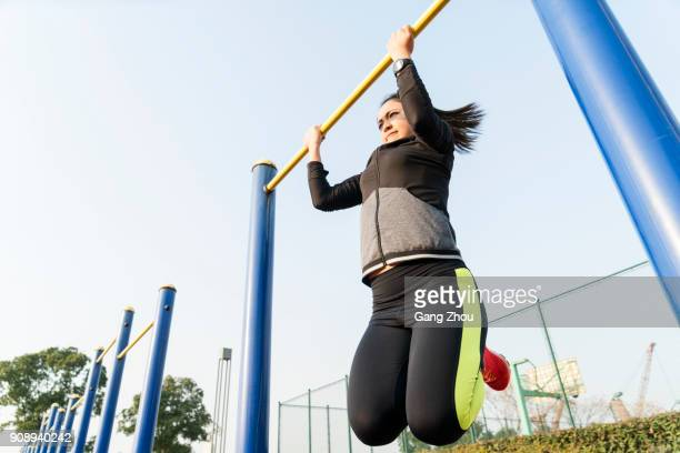 young woman hanging on horizontal bar