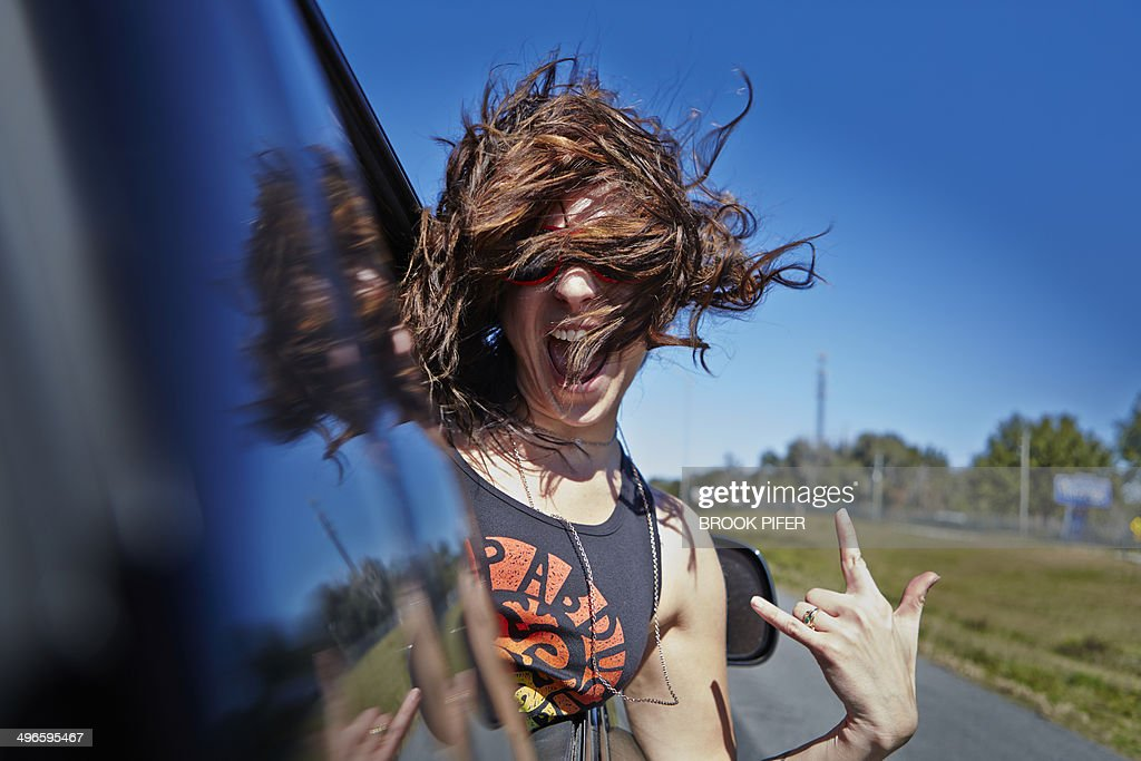 Young woman hanging out car window : Stock Photo