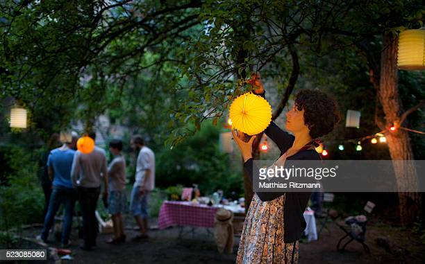 young woman hanging paper lantern on tree in back yard - garden decoration stock pictures, royalty-free photos & images