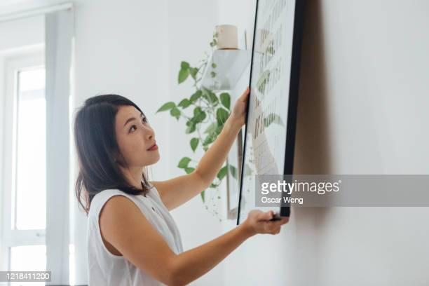 young woman hanging picture frame on wall - decor stock pictures, royalty-free photos & images