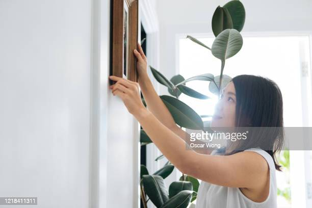 young woman hanging picture frame on wall - hanging stock pictures, royalty-free photos & images