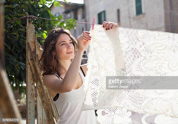 young woman hanging table cloth on clothesline - lace textile stock pictures, royalty-free photos & images