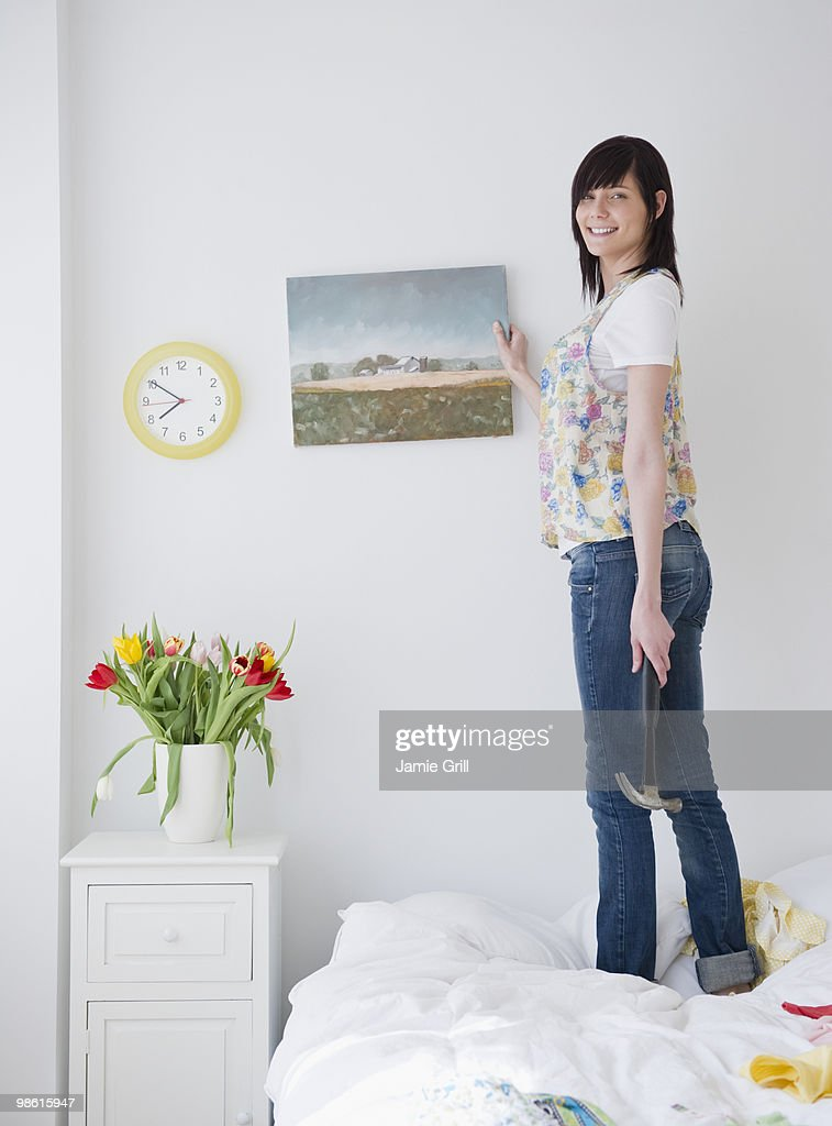 Young Woman Hanging Up Painting In Bedroom Stock Photo