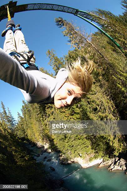 Young woman hanging upside down from bungee jump rope, portrait