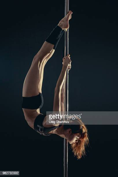 young woman hanging upside down on pole, moscow, russia - pole dance photos et images de collection