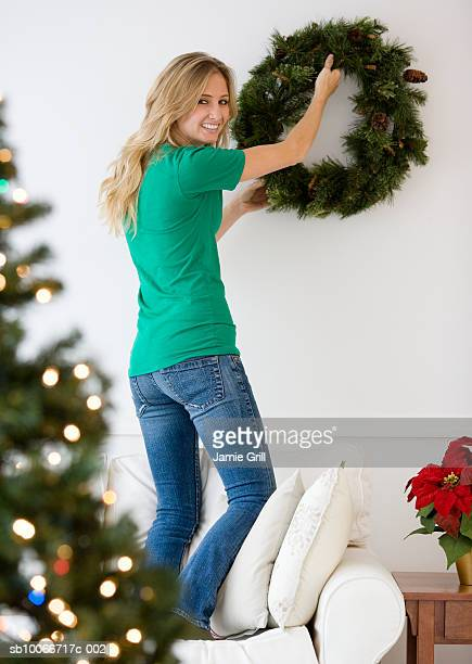 Young woman hanging wreath on wall, smiling, portrait (focus on background)