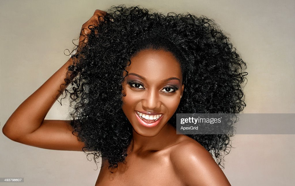 Young woman happy with curly hair on a white background
