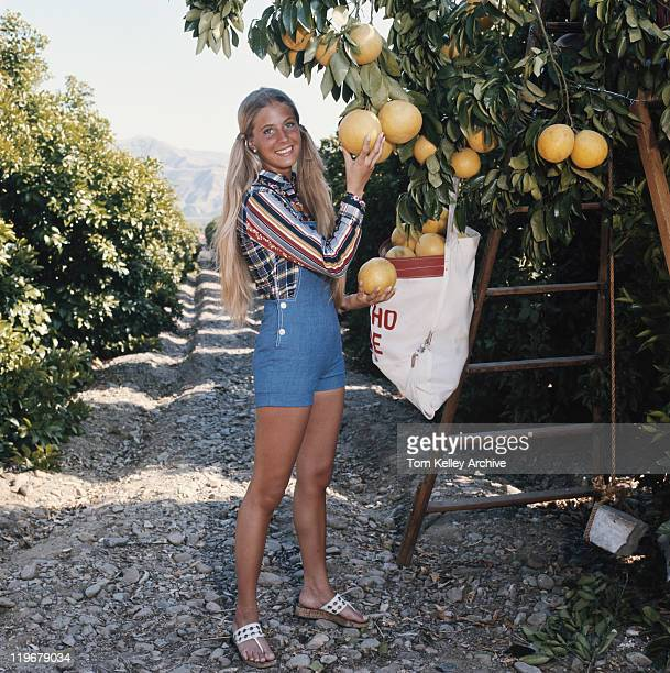 Young woman harvesting pummelo, smiling, portrait