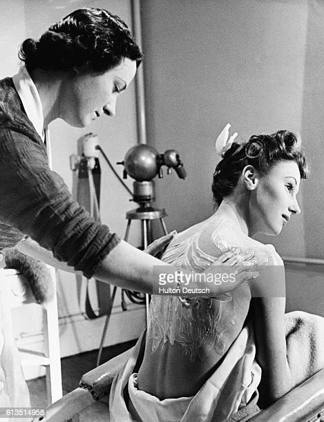 A young woman has her back massaged with a body cream by a beautician