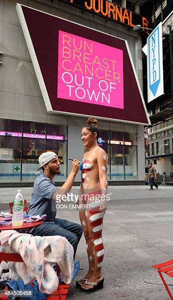 A young woman has her body painted in preparation for posing for photos with tourists in Times Square August 19 2015 in New York Mayor Bill de Blasio...
