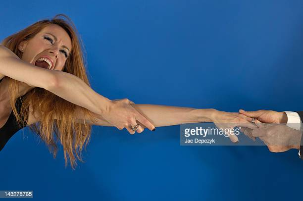 young woman has her hand forcefully pulled by man - depczyk stock pictures, royalty-free photos & images