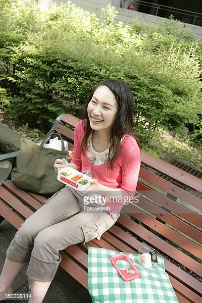 A young woman has her snacks from her lunch box while sitting on the bench