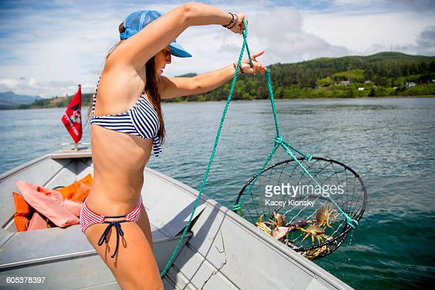 young woman hauling in crab trap on fishing boat, nehalem bay, oregon, usa - crab pot stock photos and pictures