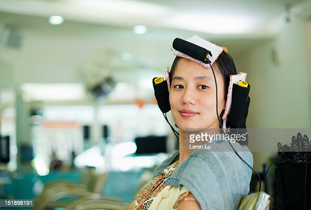 young woman have hair permed in hair salon - permed hair stock pictures, royalty-free photos & images