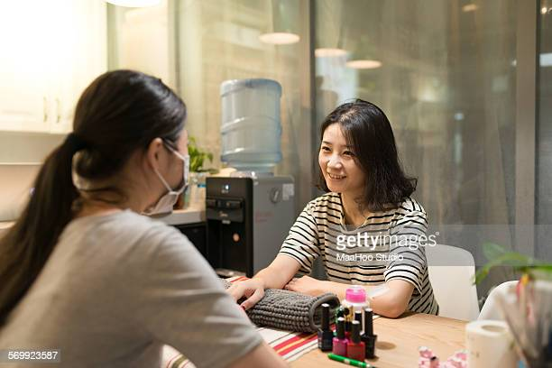 Young woman have nails done in nail salon