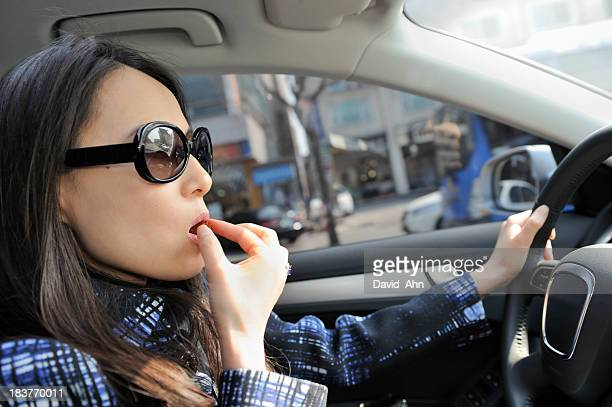Young woman having a bite while driving