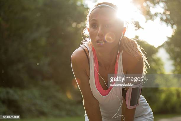 Young woman having a break after running outdoors