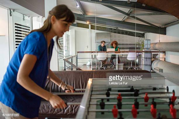 Young woman having a break playing table football in office