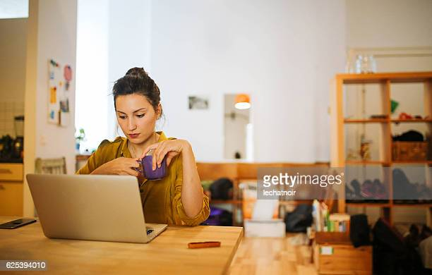 Young woman having a coffee and working at home