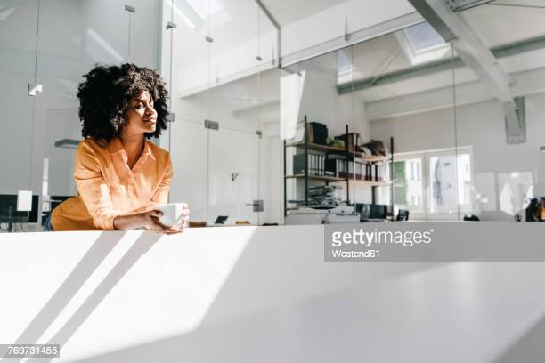young woman having a coffee break in office - pausa para o café - fotografias e filmes do acervo