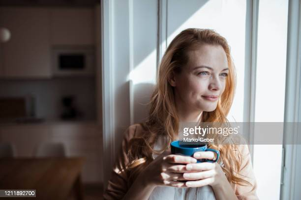 young woman having a cup of coffee - kaffee getränk stock-fotos und bilder