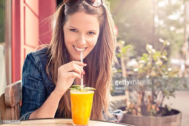 Junge Frau, die ein erfrischendes Getränk