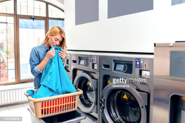 junge frau hat einen wäschetag - waschsalon stock-fotos und bilder