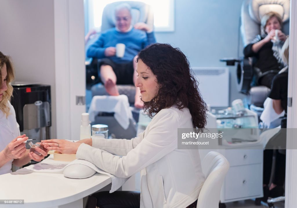 Young woman having a manucure in a beauty spa. : Stock Photo