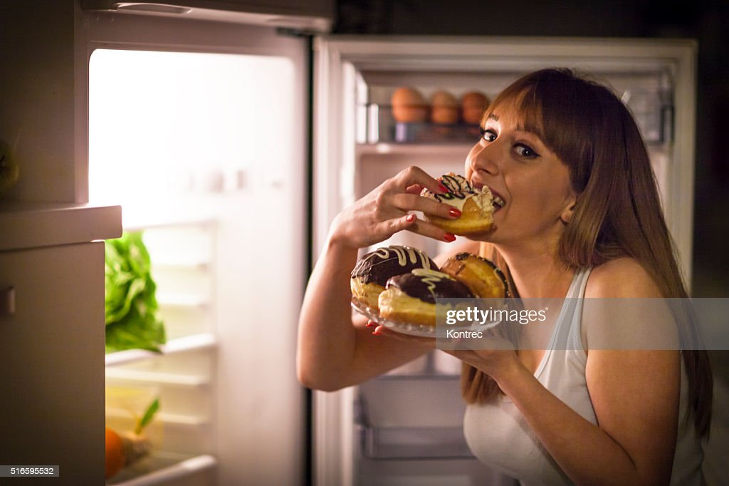 Young woman having a midnight snack : Stock Photo