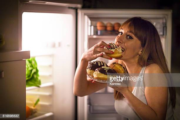 young woman having a midnight snack - sweet food stock pictures, royalty-free photos & images