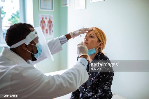 young woman having a nasal swab test - coronavirus stock pictures, royalty-free photos & images