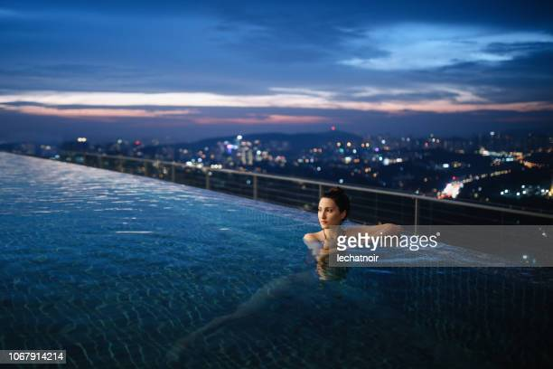 young woman having a night swim in the pool in malaysia - exclusive stock pictures, royalty-free photos & images