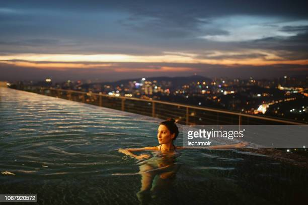 young woman having a night swim in the pool in malaysia - luxury hotel stock pictures, royalty-free photos & images