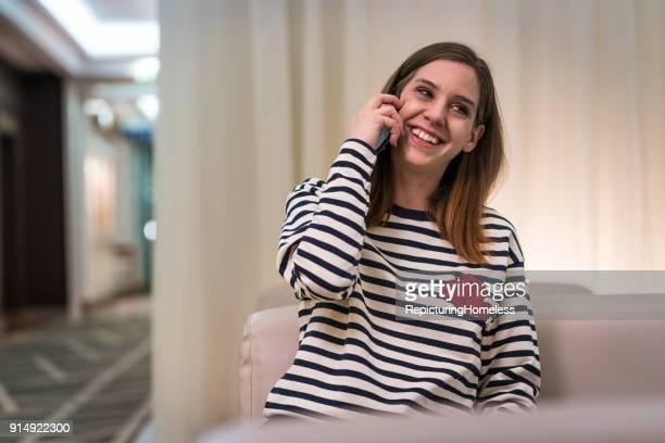 Eine junge Frau lacht beim telefonieren