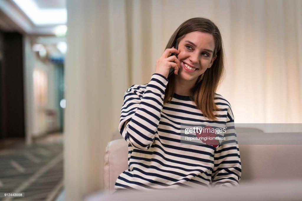 Eine junge Frau lächelt beim telefonieren : Stock-Foto
