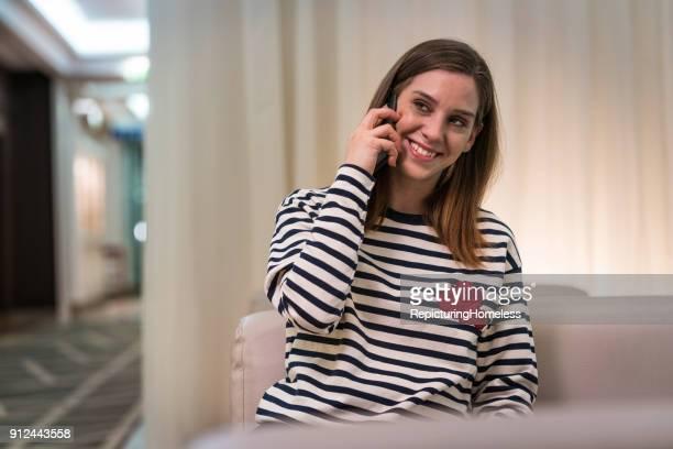 Eine junge Frau lächelt beim telefonieren
