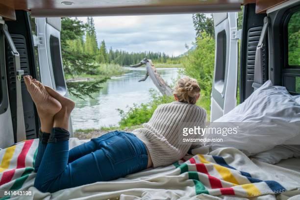 Junge Frau, die einen atemberaubenden Blick aus dem hinteren Teil ihres Camping-Van