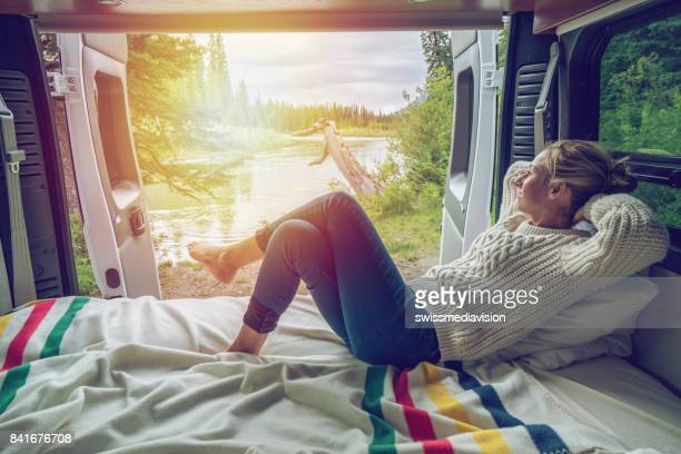 young woman having a stunning view out of the back of her camping van - camping stock photos and pictures