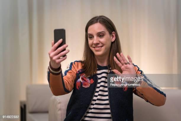 eine junge frau versucht ein selfie zu schießen - repicturing homeless stock-fotos und bilder
